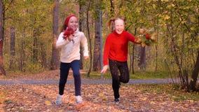 Ευτυχή λατρευτά κορίτσια που τρέχουν με τις ανθοδέσμες φύλλων στο πάρκο φθινοπώρου σε σε αργή κίνηση απόθεμα βίντεο