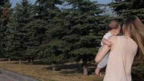 Ευτυχή μητέρα και μωρό που περπατούν υπαίθρια στη θερινή ημέρα απόθεμα βίντεο