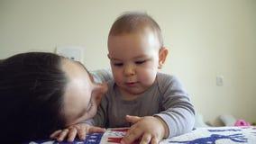 Ευτυχή μητέρα και μωρό που φιλούν και που αγκαλιάζουν τη μητρότητα που λειτουργεί mom με τα ασύρματα ακουστικά 4k φιλμ μικρού μήκους