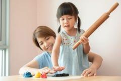 Ευτυχή μητέρα και παιδί που προετοιμάζουν τη ζωηρόχρωμη ζύμη στοκ εικόνες