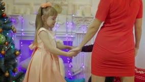 Ευτυχή μητέρα και παιδιά που χορεύουν στο υπόβαθρο του χριστουγεννιάτικου δέντρου φιλμ μικρού μήκους
