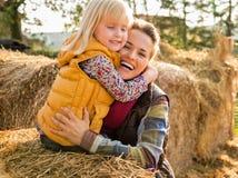 Ευτυχή μητέρα και παιδί που αγκαλιάζουν ενώ στη θυμωνιά χόρτου στοκ εικόνα