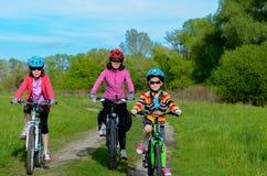 Ευτυχή μητέρα και παιδιά στα ποδήλατα που ανακυκλώνουν υπαίθρια Στοκ Εικόνες