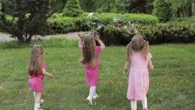 Ευτυχή μικρά κορίτσια που παίζουν στις φυσαλίδες κήπων και παιχνιδιού απόθεμα βίντεο
