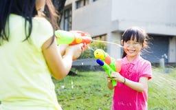Ευτυχή μικρά κορίτσια που παίζουν τα πυροβόλα όπλα νερού στο πάρκο Στοκ εικόνες με δικαίωμα ελεύθερης χρήσης