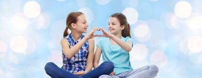 Ευτυχή μικρά κορίτσια που παρουσιάζουν σημάδι χεριών μορφής καρδιών Στοκ Εικόνες