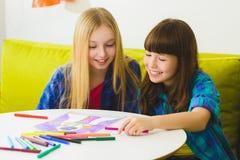 Ευτυχή μικρά κορίτσια που σύρουν τις εικόνες Εσωτερικός στο δωμάτιο Στοκ φωτογραφία με δικαίωμα ελεύθερης χρήσης