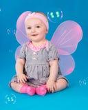 Ευτυχή μικρά φτερά πεταλούδων κοριτσιών που κάθονται στο πάτωμα Στοκ Φωτογραφίες