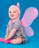 Ευτυχή μικρά φτερά πεταλούδων κοριτσιών που κάθονται στο πάτωμα Στοκ Φωτογραφία
