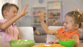 Ευτυχή μικρό παιδί και κορίτσι που ρίχνουν τα δημητριακά μεταξύ τους, που έχει τη διασκέδαση στο σπίτι απόθεμα βίντεο