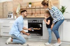 Ευτυχή μπισκότα οικογενειακού ψησίματος στο φούρνο στοκ φωτογραφία με δικαίωμα ελεύθερης χρήσης
