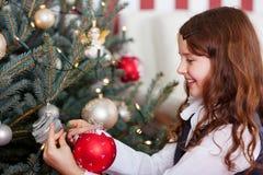 Ευτυχή μπιχλιμπίδια Χριστουγέννων κοριτσιών κρεμώντας Στοκ εικόνα με δικαίωμα ελεύθερης χρήσης