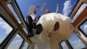 Ευτυχή νέα εύθυμα κυματίζοντας χέρια και πόδια γαμήλιων ζευγών στην αναδρομική κορυφή λεωφορείων στον τομέα Όψη από κάτω από Ευτυ απόθεμα βίντεο