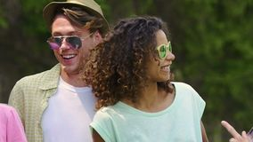 Ευτυχή νέα ζεύγη που χορεύουν και που χαμογελούν στο πάρκο, καλοκαιρινές διακοπές, νεολαία απόθεμα βίντεο