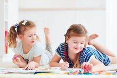 Ευτυχή νέα κορίτσια, παιδιά που χρωματίζουν με την αισθητή μάνδρα από κοινού Στοκ εικόνες με δικαίωμα ελεύθερης χρήσης