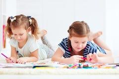 Ευτυχή νέα κορίτσια, παιδιά που χρωματίζουν με την αισθητή μάνδρα από κοινού Στοκ Εικόνες