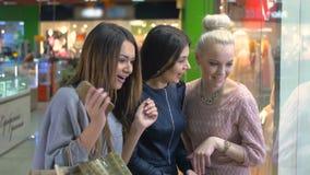 Ευτυχή νέα κορίτσια που εξετάζουν αναστατωμένα την προθήκη, προθήκη Καταναλωτισμός και έννοια ανθρώπων απόθεμα βίντεο