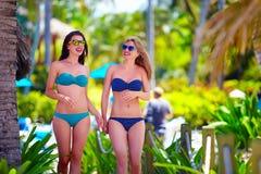 Ευτυχή νέα κορίτσια που περπατούν στην τροπική παραλία, κατά τη διάρκεια των θερινών διακοπών Στοκ Εικόνες