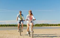 Ευτυχή νέα οδηγώντας ποδήλατα ζευγών στην παραλία Στοκ εικόνες με δικαίωμα ελεύθερης χρήσης