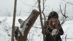 Ευτυχή νέα παιχνίδια γυναικών με ένα χιόνι στο όμορφο χειμερινό δάσος φιλμ μικρού μήκους