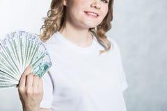 Ευτυχή νέα χρήματα αμερικανικών δολαρίων λαβής γυναικών χαμόγελου υπό εξέταση πέρα από το άσπρο υπόβαθρο στοκ εικόνα