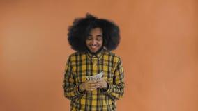 Ευτυχή νέα χρήματα εκμετάλλευσης ατόμων αφροαμερικάνων στα χέρια του και εξέταση τη κάμερα στο πορτοκαλί υπόβαθρο απόθεμα βίντεο