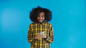 Ευτυχή νέα χρήματα εκμετάλλευσης ατόμων αφροαμερικάνων στα χέρια του και εξέταση τη κάμερα στο μπλε υπόβαθρο απόθεμα βίντεο