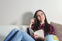Ευτυχή νέα όνειρα γυναικών brunette διακοπών ταξιδιών που βρίσκονται σε έναν άσπρο καναπέ με ένα ημερολόγιο Στοκ εικόνες με δικαίωμα ελεύθερης χρήσης