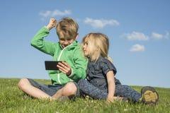 Ευτυχή ξανθά παιδιά που χρησιμοποιούν τη συνεδρίαση smartphone (κινηματογράφος προσοχής ή παίζοντας παιχνίδι) στη χλόη Στοκ Εικόνες