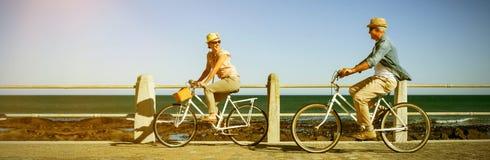 Ευτυχή οδηγώντας ποδήλατα ζευγών στην αποβάθρα Στοκ φωτογραφία με δικαίωμα ελεύθερης χρήσης