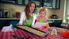Ευτυχή οικογενειακά κορίτσια που ψήνουν τα μπισκότα και που εξετάζουν τον επιτραπέζιο υπολογιστή απόθεμα βίντεο