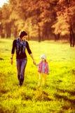 Ευτυχή οικογενειακά μητέρα και παιδί λίγη κόρη που περπατά στο φθινόπωρο Στοκ εικόνες με δικαίωμα ελεύθερης χρήσης