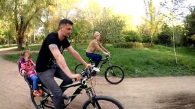 Ευτυχή οικογενειακά οδηγώντας ποδήλατα στο πάρκο απόθεμα βίντεο