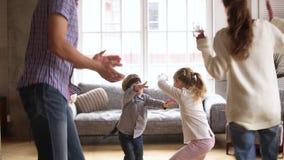 Ευτυχή οικογενειακά παιδιά που παίζουν τη δορά και το παιχνίδι χειροκροτήματος στο σπίτι απόθεμα βίντεο