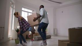 Ευτυχή οικογενειακά φέρνοντας κιβώτια που κινούνται στο καινούργιο σπίτι απόθεμα βίντεο