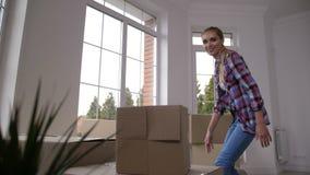 Ευτυχή οικογενειακά φέρνοντας κουτιά από χαρτόνι στο καινούργιο σπίτι απόθεμα βίντεο