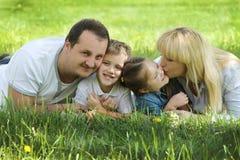 Ευτυχή οικογενειακά φιλώντας παιδιά πέρα από πράσινο Στοκ Εικόνες