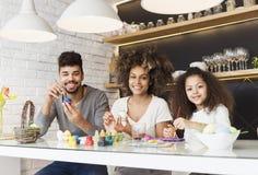 Ευτυχή οικογενειακά χρωματίζοντας αυγά αφροαμερικάνων Στοκ Εικόνες