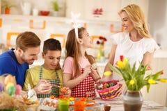 Ευτυχή οικογενειακά χρωματίζοντας αυγά για Πάσχα στοκ εικόνες