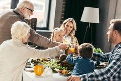 ευτυχή οικογενειακά clinking γυαλιά Στοκ φωτογραφία με δικαίωμα ελεύθερης χρήσης