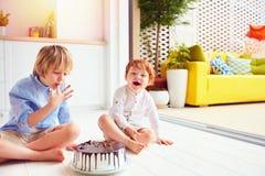 Ευτυχή παιδιά, αδελφοί που δοκιμάζουν το κέικ γενεθλίων στο σπίτι Στοκ φωτογραφία με δικαίωμα ελεύθερης χρήσης