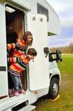 Ευτυχή παιδιά κοντά στο τροχόσπιτο (rv) που έχει τη διασκέδαση Στοκ Εικόνες