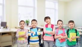 Ευτυχή παιδιά με τις σχολικά τσάντες και τα σημειωματάρια στοκ φωτογραφίες με δικαίωμα ελεύθερης χρήσης