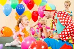 Ευτυχή παιδιά με τον κλόουν στη γιορτή γενεθλίων Στοκ Φωτογραφίες