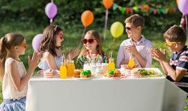 Ευτυχή παιδιά με το κέικ στη γιορτή γενεθλίων στο καλοκαίρι Στοκ Εικόνα