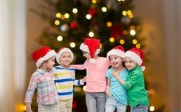 Ευτυχή παιδιά πέρα από τα φω'τα χριστουγεννιάτικων δέντρων στοκ εικόνες