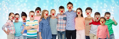 Ευτυχή παιδιά που αγκαλιάζουν στην κόκκινη ημέρα μύτης στοκ εικόνες