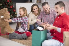 Ευτυχή παιδιά που ανοίγουν τα δώρα Χριστουγέννων Στοκ εικόνα με δικαίωμα ελεύθερης χρήσης