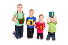 Ευτυχή παιδιά που κρατούν τους φραγμούς με τους αριθμούς πέρα από το άσπρο υπόβαθρο Στοκ Εικόνα