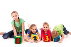 Ευτυχή παιδιά που κρατούν τους φραγμούς με τους αριθμούς πέρα από το άσπρο υπόβαθρο Στοκ φωτογραφία με δικαίωμα ελεύθερης χρήσης